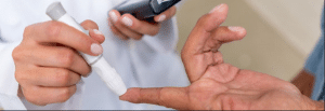 Close up photograph of a doctor pricking someone's fingertip